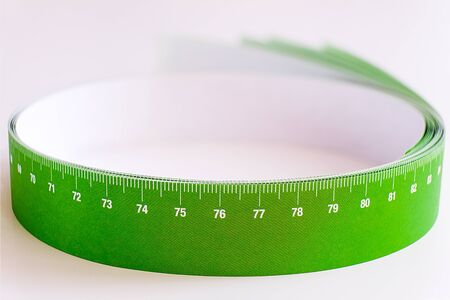 Meter tape for measuring rolled into a roll, on a light background. Selective focus