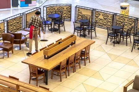 Cafe cleaning at the end of the working day. Sweeping debris and wet floor cleaning