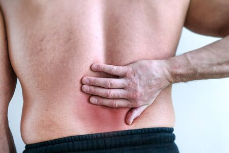 Red back pain on a light background. Isolated background. Sports physical therapy. Concept of physical trauma. The concept of pain
