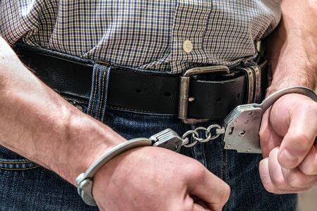The criminal was detained by the police. The handcuffed hands clenched into fists