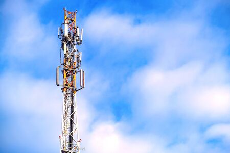Antenna of the telecommunications tower. Communication network. Technology at the top of GSM telecommunications. Masts for mobile phone signal. Tower with cellular antennas on a blue sky background