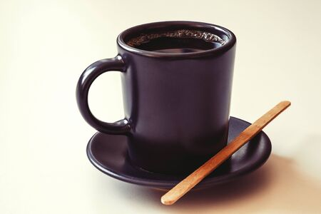 A Cup of espresso. Wooden bamboo stirring stick. Morning invigorating drink