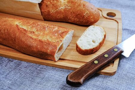 Fresh warm baguette with a crispy crust. Sliced for Breakfast. For the morning sandwich. Banco de Imagens