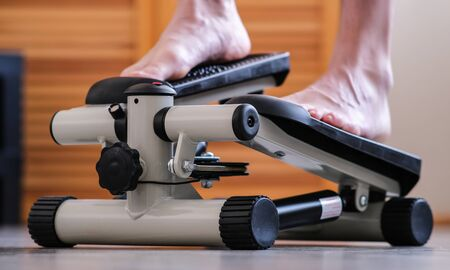 The feet of the feet press on the pedals of the rehabilitation simulator. Recovery of the ankle after an injury Stock Photo