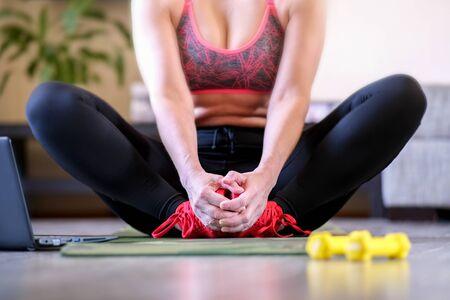 Yoga asana. Pranayama breath. Fitness training online on a laptop computer. The girl in quarantine monitors her athletic form