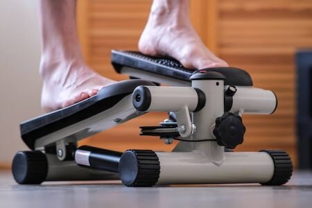 Leg training. The feet of the feet press on the pedals of the rehabilitation simulator. Recovery of the ankle joint after injury