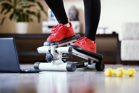 Online fitness training on a step-simulator. Sports activities at home during the quarantine period