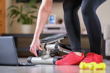 The girl turns the handle of the step simulator increases the load. Online fitness training on a step-simulator. Sports at home during the quarantine period