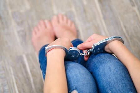 The concept of violence against women, hands cuffed. Domestic violence is a real action, a threat of physical, sexual, and psychological pressure. A husband holds his wife in handcuffs