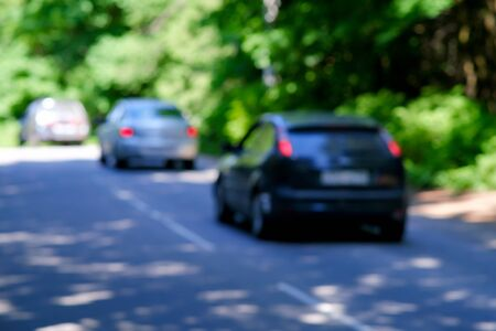 Background, blur, out of focus, bokeh. Soft sunlight through the trees in the forest. Cars are driving on a forest highway Stock Photo