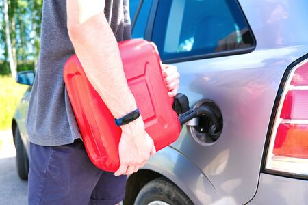 Red canister in the hands of a man. Filling a stalled car with gasoline from a canister