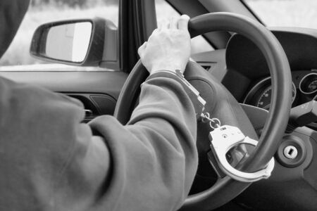 Black and white photo. The hijacker is handcuffed to the steering wheel. The criminal was caught stealing a car. The police did a good job Stockfoto