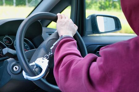 The criminal was caught stealing a car. The hijacker is handcuffed to the steering wheel. The police did a good job Stockfoto