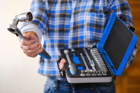 A locksmith in a checked shirt holds a key in his hand. Universal key for any locksmith work. Stockfoto