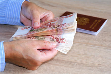 A person received a loan from a Bank, counting bills. The passport is on the table. Archivio Fotografico - 151072601