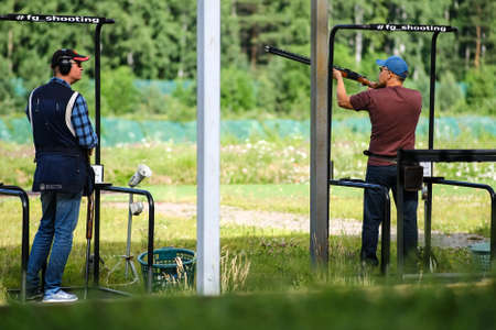 Two shooters in the shooting range of the bench. The man is wearing headphones, the second is ready to shoot. Saint-Petersburg. Russia. July 8, 2020. Editöryel