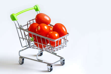 Tomatoes in a grocery cart. A shopping basket filled with fresh vegetables is isolated. The concept of healthy eating. Banque d'images