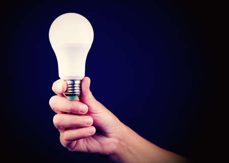 Led energy-saving light bulb in the hand of a person. The concept of modern economical lighting