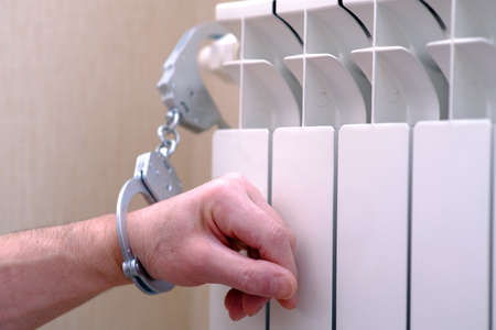 Handcuffs on the hand. The hand is handcuffed to the radiator of the heater. The concept of self-isolation during a pandemic