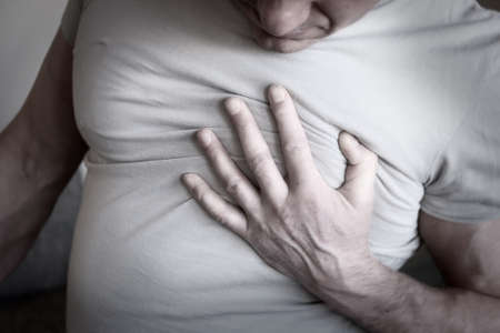 The man clutched at his chest. Heart attack angina on a white background. Sick person. Medical examination. Heart disease