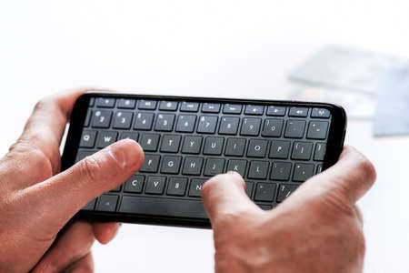 Smartphone with keyboard in English. A person with a phone makes an online order Stock fotó - 152493054