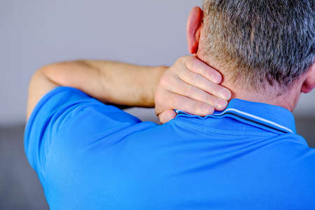 Pain in the neck, the man massages the place of inflammation with his hand Foto de archivo