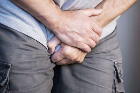 A man holds his groin with both hands, an attack of urological pain in the bladder