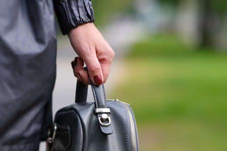 Elegant outfit. Close up of stylish gray backpack in woman s hand. Model holding bag and sitting on the green grass. Female fashion concept. Banco de Imagens