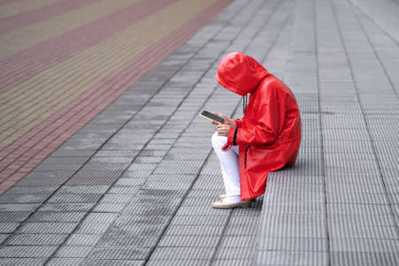 A young woman in a red raincoat pulled a hood over her head to hide from the rain. Sitting on the steps, Smoking, looking at the smartphone. Banco de Imagens