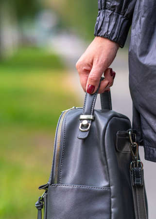 Elegant outfit. Close up of stylish gray backpack in woman s hand. Model holding bag and sitting on the green grass. Female fashion concept