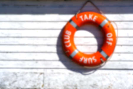 Background, blur, out of focus, bokeh. Orange rescue float. Lifebuoy on the wall of the building of the rescue station