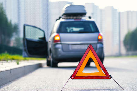 Triangular red retro-reflective sign of accident on the road. Car accident on the street
