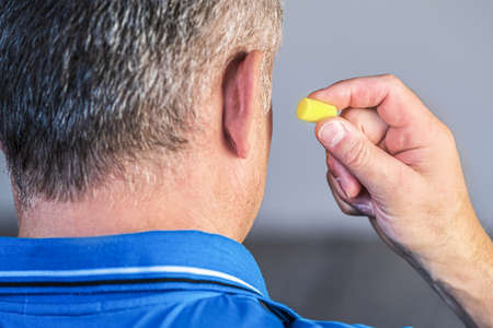 Close - up of a mans ear with a yellow earplug in his hand.