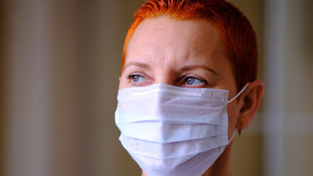 Medical mask on the girls face. Personal protective equipment. The concept of preventing the spread of the virus during an epidemic.