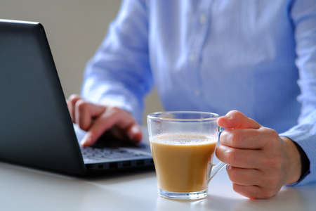 The girl finishes working at the computer for a time out over a Cup of coffee. Banco de Imagens