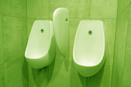 Modern urinal sinks in the toilet with green lighting.