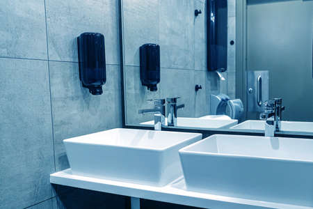 Modern sinks with a mirror in a public toilet. Bachelors reflection in the mirrors.
