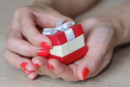 Red gift box of a womans hands in a beautiful style on a light background. Great design for gift purposes. The concept of the celebration