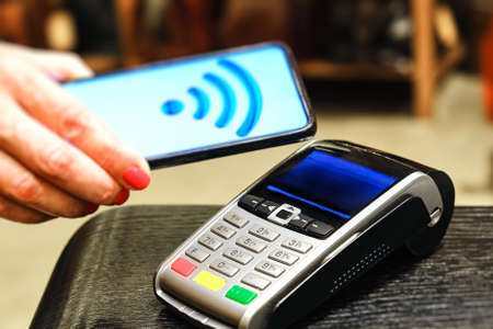 Payment by smartphone in the payment terminal. Electronic money. Mobile banking. Shopping complex.
