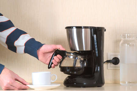 Coffee area in the office. The Manager pours a Cup of coffee from a glass coffee flask during a timeout