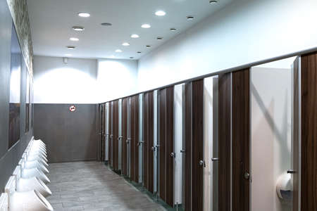 Cubicles of the toilets in the shopping complex. On the wall is a row of urinals. On the wall a sticker banning Smoking