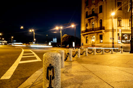 Granite posts with chains. Abstract night city blurred lights of moving cars for decoration design. Yellow background. Abstract background. The dark blue sky