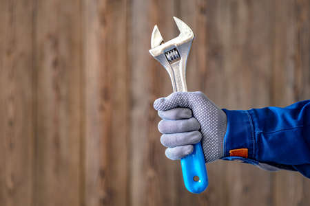 The master holds in his hand an adjustable locksmith key with a blue handle. Locksmith repair work