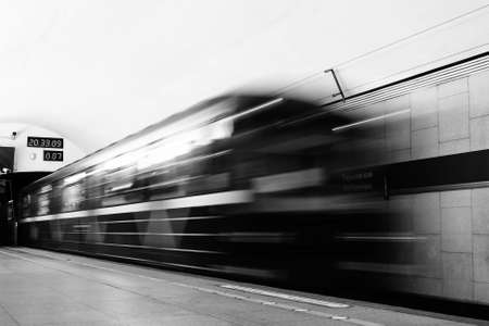 Black and white photo. Blurred cars of the outgoing train on the metro platform.