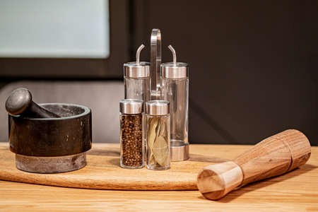Mortar and pestle pepper shaker and mill on the table. Kitchen utensils for cooking in a modern style on a dark background. Home decor design. Modern home decor