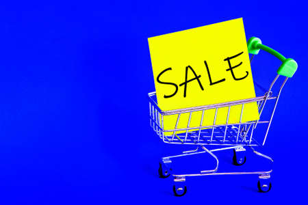 Shopping cart from the supermarket. Discount on Black Friday. Sales of products of all categories. Advertising design for the banner. Poster design. Blue background