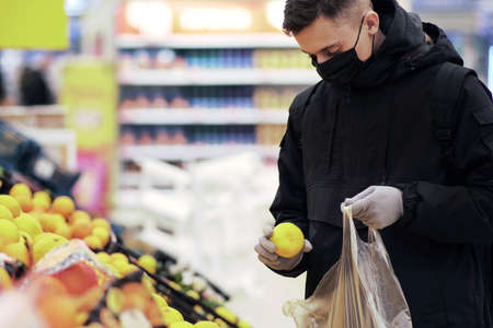 A young man wearing a mask and protective gloves buys food at a store