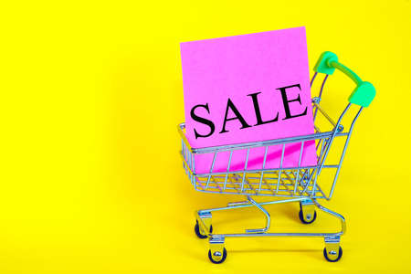 Sticker with the words discount, in the basket from the supermarket. Sales of products of all categories. Advertising design for the banner. Poster design. Yellow background Banque d'images