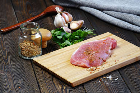 Fresh steak is on the cutting Board. Escalope is prepared for frying in a frying pan. Near seasonings and ingredients for cooking