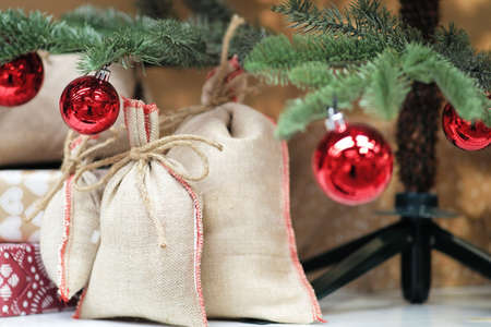 Wrapped gifts under the Christmas tree. Canvas bags, surprise gifts for children